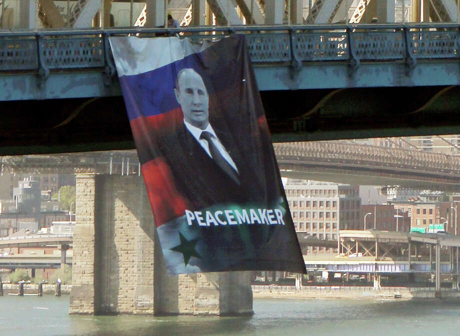 "In this photo provided by Gothamist.com, a banner bearing an image of Russian President Vladimir Putin showing him with a Russian and Syrian flag as backdrop and labeling him a ""peacemaker"" hangs from the Manhattan Bridge, Thursday, Oct. 6, 2016, in New York.  Witnesses told the New York Post they saw two people unfurl the banner at about 1:45 p.m. Thursday. Police say officers removed the banner about an hour later. No arrests have been made, but investigation is continuing according to police. Photo: Nathan Tempey/AP"