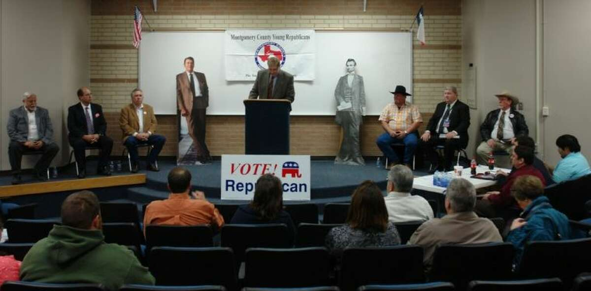 Montgomery County Young Republican Public Relations Director Kurt Jones opened the candidate forum Thursday night at Caney Creek High School. Seated are the Montgomery County Commissioner Precinct 4 candidates (from left to right) Bob Bagley, David Miller, Clarence Quinn, Jones, Darrin Holy, Jim Clark and Roland
