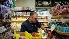 Sam Mogannam, owner of Bi-Rite grocery re-stocks the strawberries at the Bi-Rite in the Mission, in San Francisco, California, on Wednesday, Oct. 5, 2016.