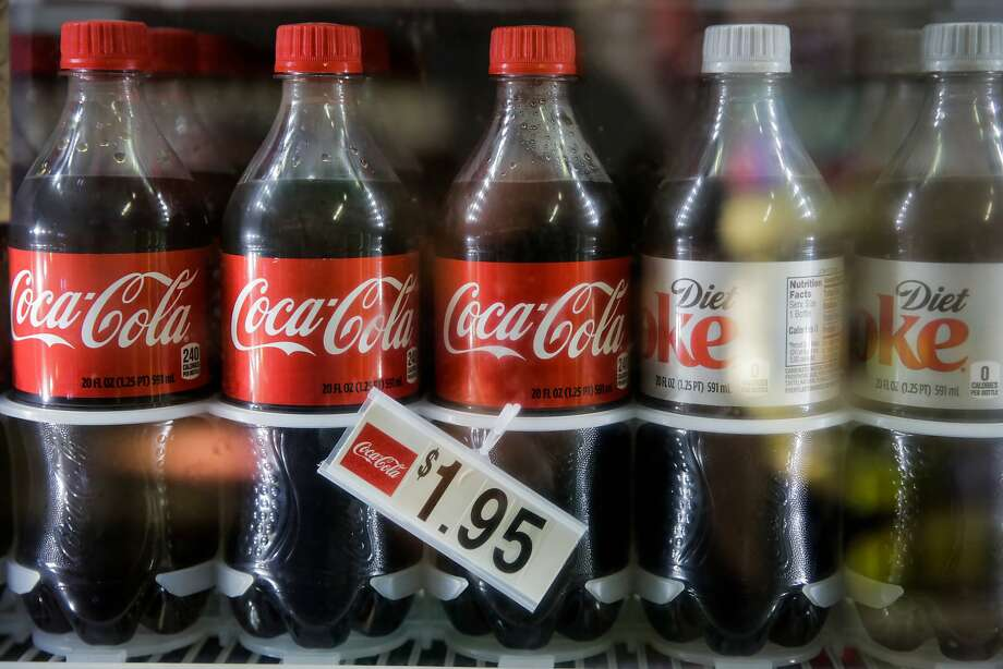 Bottles of Coca-Cola and Diet Coke sit in a refrigerator at Mi Rancho Produce in the Mission District in San Francisco. Most grocers say they will not raise prices on all products if the soda tax passes. Photo: Gabrielle Lurie, The Chronicle