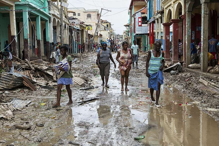 People walk down a flooded street in Jeremie, a city that suffered the full force of the Category 4 storm that tore through the area with winds of 145 mph. Photo: LOGAN ABASSI, AFP/Getty Images