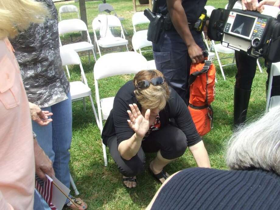 Merry Zoe Underland prays for local man who passed out after the National Day of Prayer ceremony ended on Thursday, May1, 2014