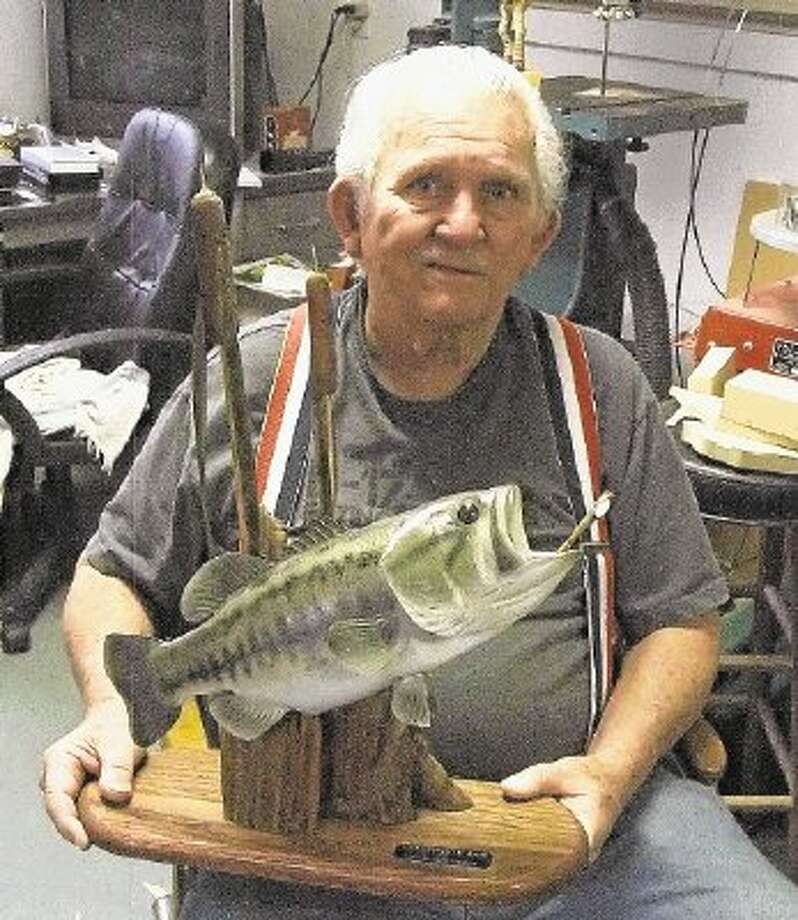 Dub Johnson holding a largemouth bass complete with cattails and a dragonfly about to be eaten. A woodcarving like that is valued at around $750.00. / @WireImgId=2658868
