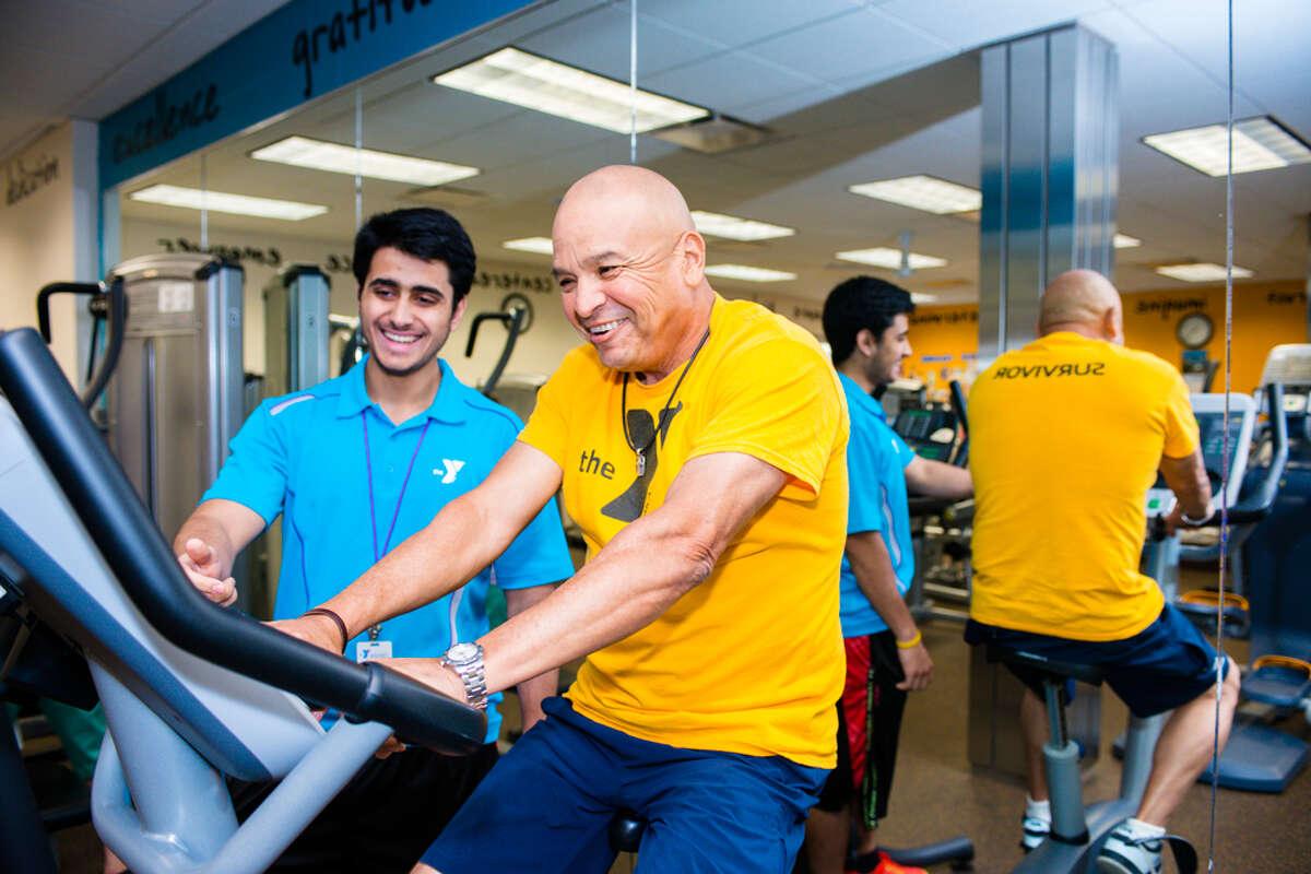 A LIVESTRONG at the YMCA coach helps a cancer survivor exercise during a LIVESTRONG class.