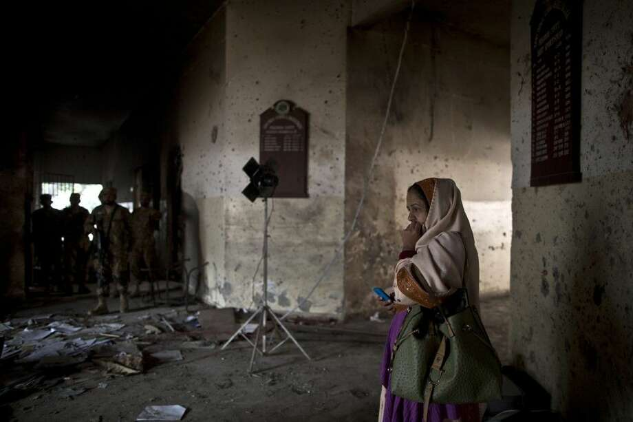A Pakistani woman on Thursday looks at the damage inside the Army Public School, attacked Tuesday by Taliban gunmen in Peshawar, Pakistan. The Taliban killed more than 140 people, mostly children, at the military-run school in northwestern Pakistan. Photo: Muhammed Muheisen
