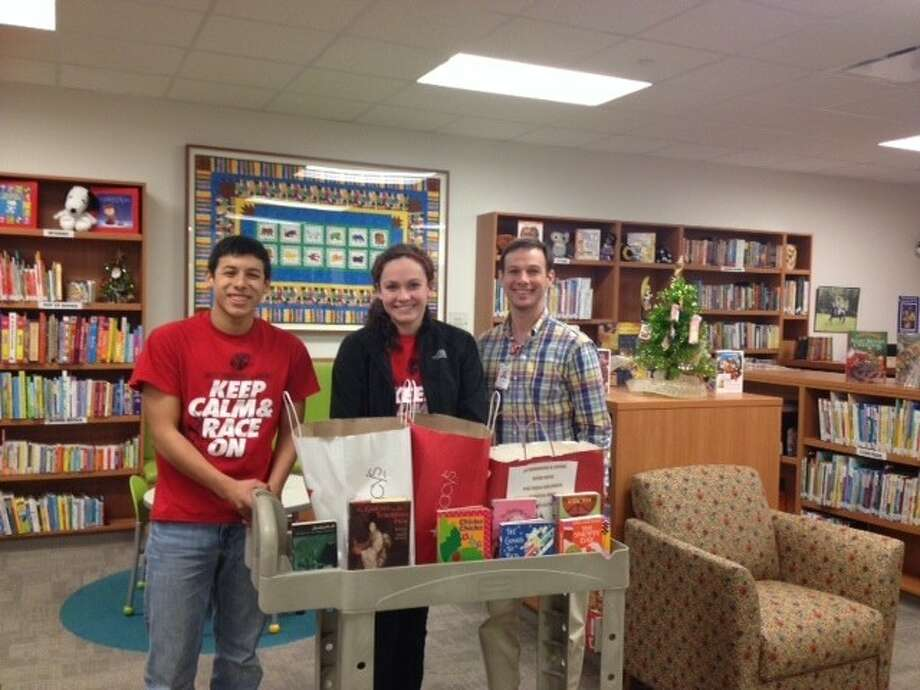 Katy Tigers Philip Garza (left) and Caroline Benson (middle), present donated books to Brian Ballard (right), Library Coordinator for Texas Children's Hospitals. Photo: Submitted