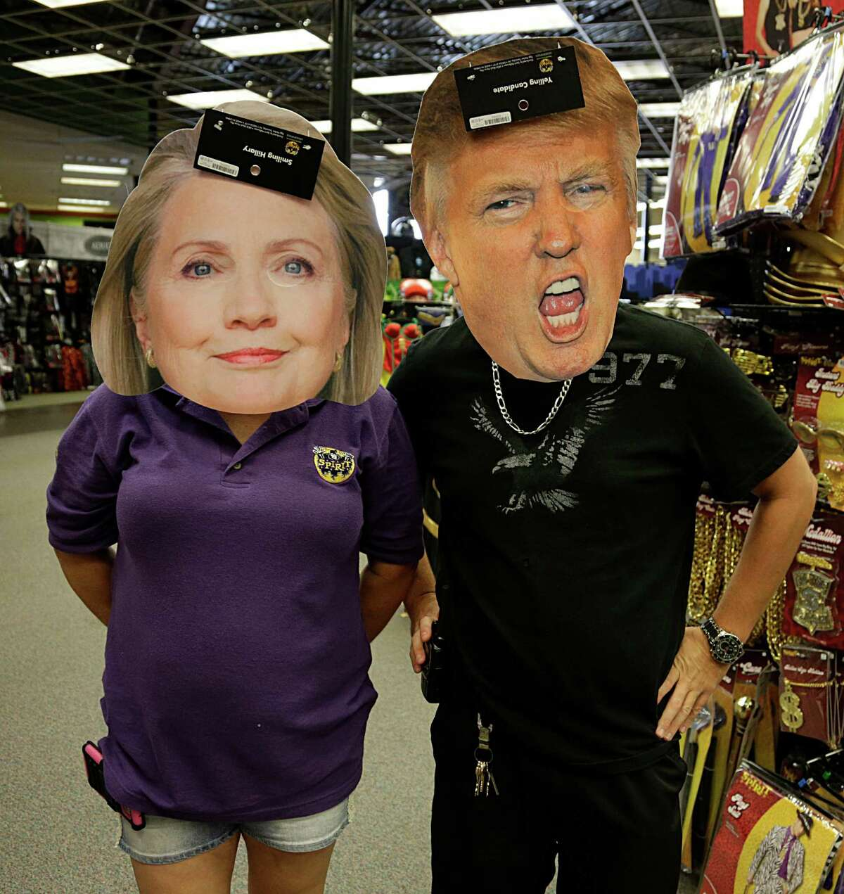 A Spirit Halloween store, managers wear Hillary Clinton and Donald Trump mask Oct. 7, 2016, in Houston.