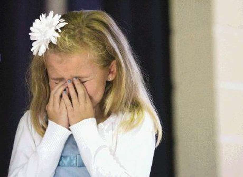 Faith Hays, 9, reacts as the 911 call she made is replayed during a school assembly at Sally K. Ride Elementary School in The Woodlands Friday. Faith was honored during the assembly for calling 911 after her mother had a seizure at their home.
