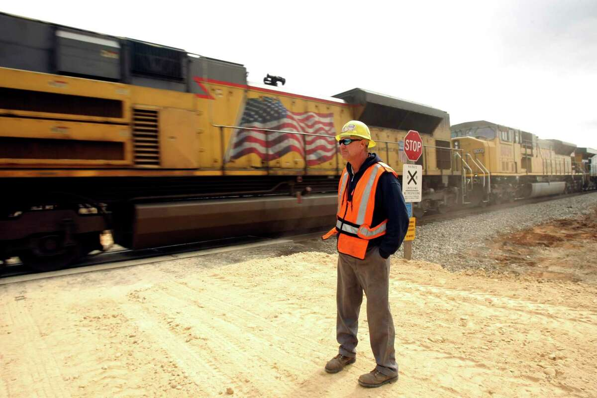 Skeeter Tatzlaff watches as a train passes by south of Cotulla. The