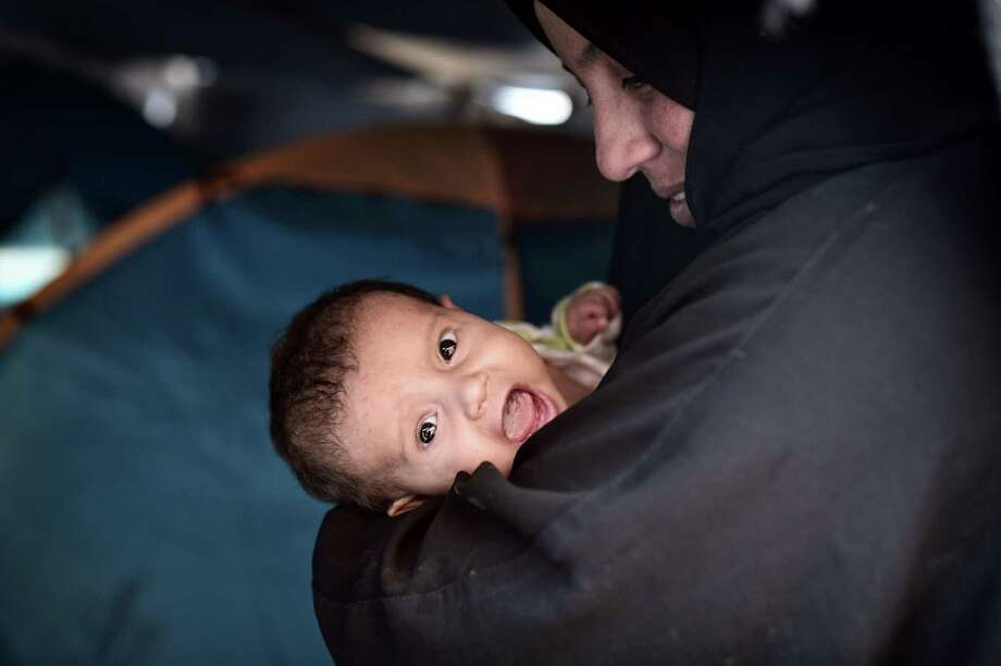 A Syrian woman holds her four-week old baby at the municipality-run Souda refugee camp in Greece. A reader defends the push by Texas officials to keep refugees out. Photo: LOUISA GOULIAMAKI /AFP /Getty Images / AFP or licensors