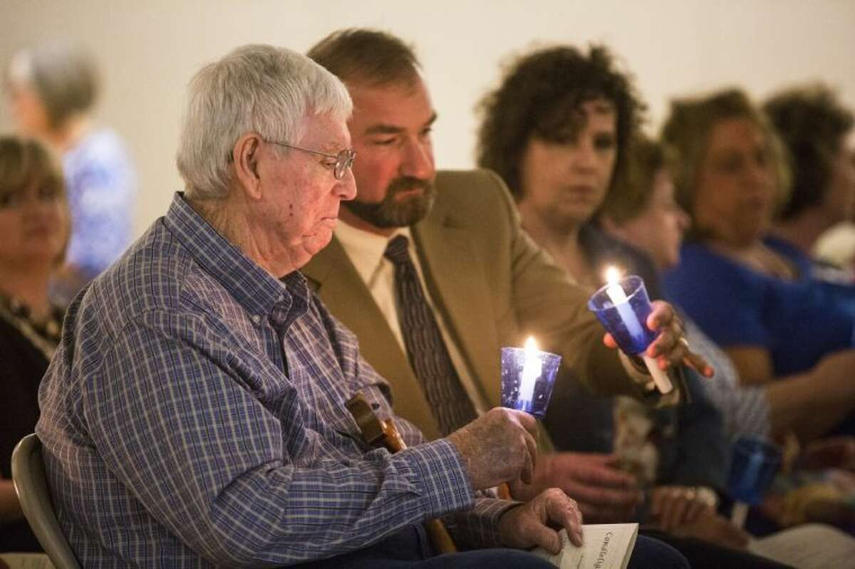 Tommy McMullan, left, and Liberty ISD Superintendent Cody Abshier light their candles during a candlelight vigil in recognition of Child Abuse Prevention Month and Crime Victims' Rights Week on April 8, 2014, at Liberty Center.
