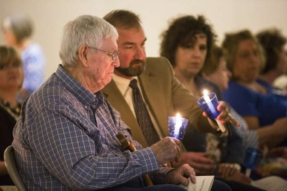 Tommy McMullan, left, and Liberty ISD Superintendent Cody Abshier light their candles during a candlelight vigil in recognition of Child Abuse Prevention Month and Crime Victims' Rights Week on April 8, 2014, at Liberty Center. Photo: ANDREW BUCKLEY