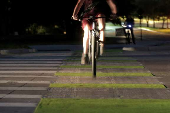 A bicylclist rides down new  bike lanes at the intersection of Bizzell and Ross Streets on the Texas A&M campus in College Station on Oct. 5.