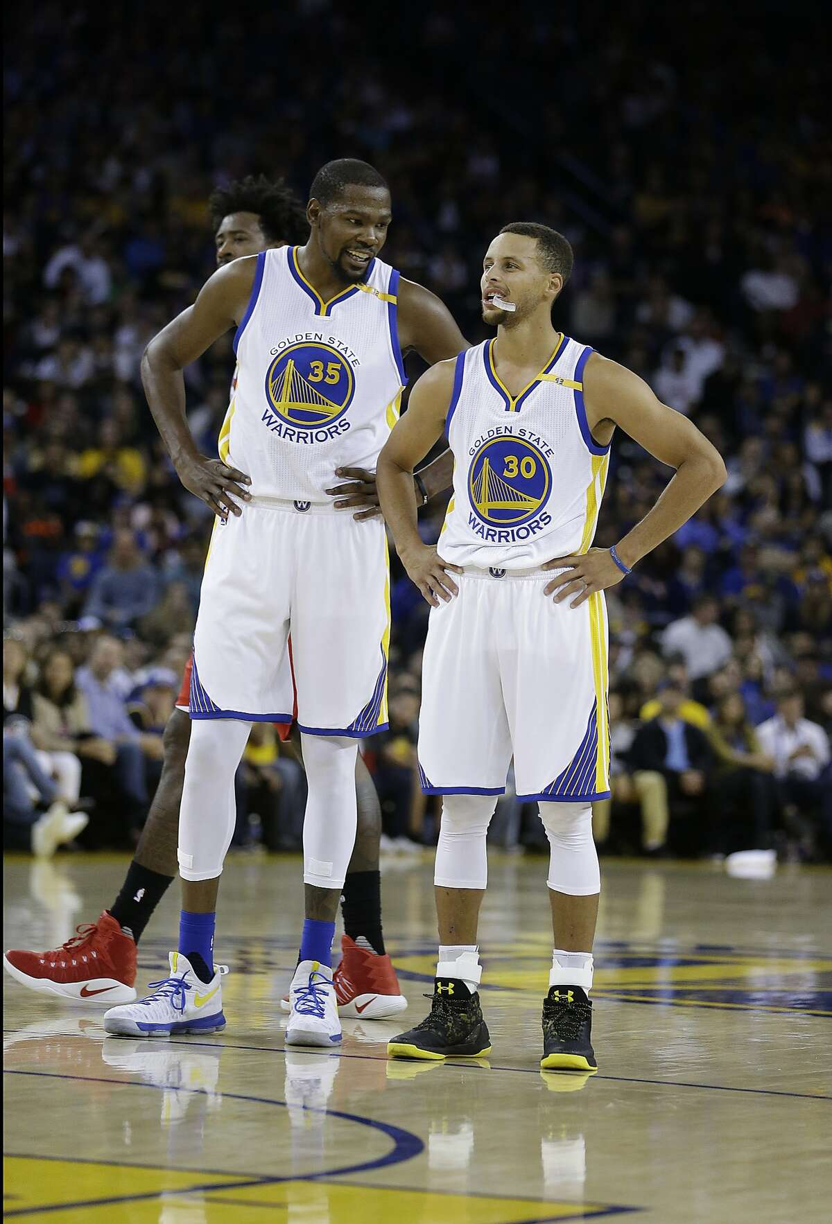 Golden State Warriors' Kevin Durant, left, speaks with Stephen Curry (30) during the first half of a pre-season NBA basketball game against the Los Angeles Clippers Tuesday, Oct. 4, 2016, in Oakland, Calif. (AP Photo/Ben Margot)