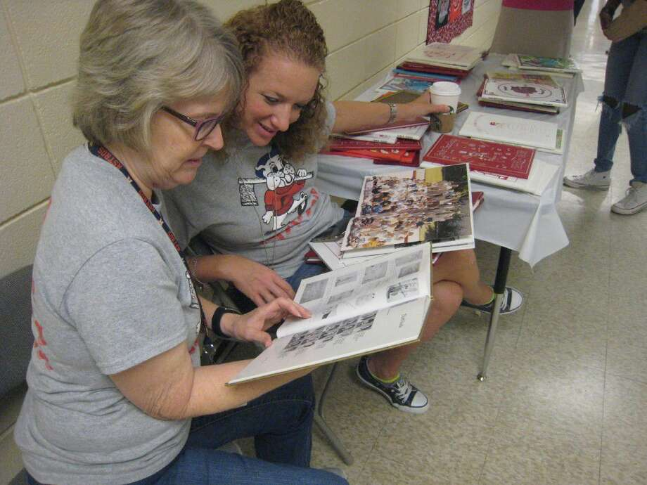 Sara Brent, left, and Kelly Tomasino look through yearbooks at the 45th anniversary celebration of Foster Elementary in Kingwood Sept. 17.