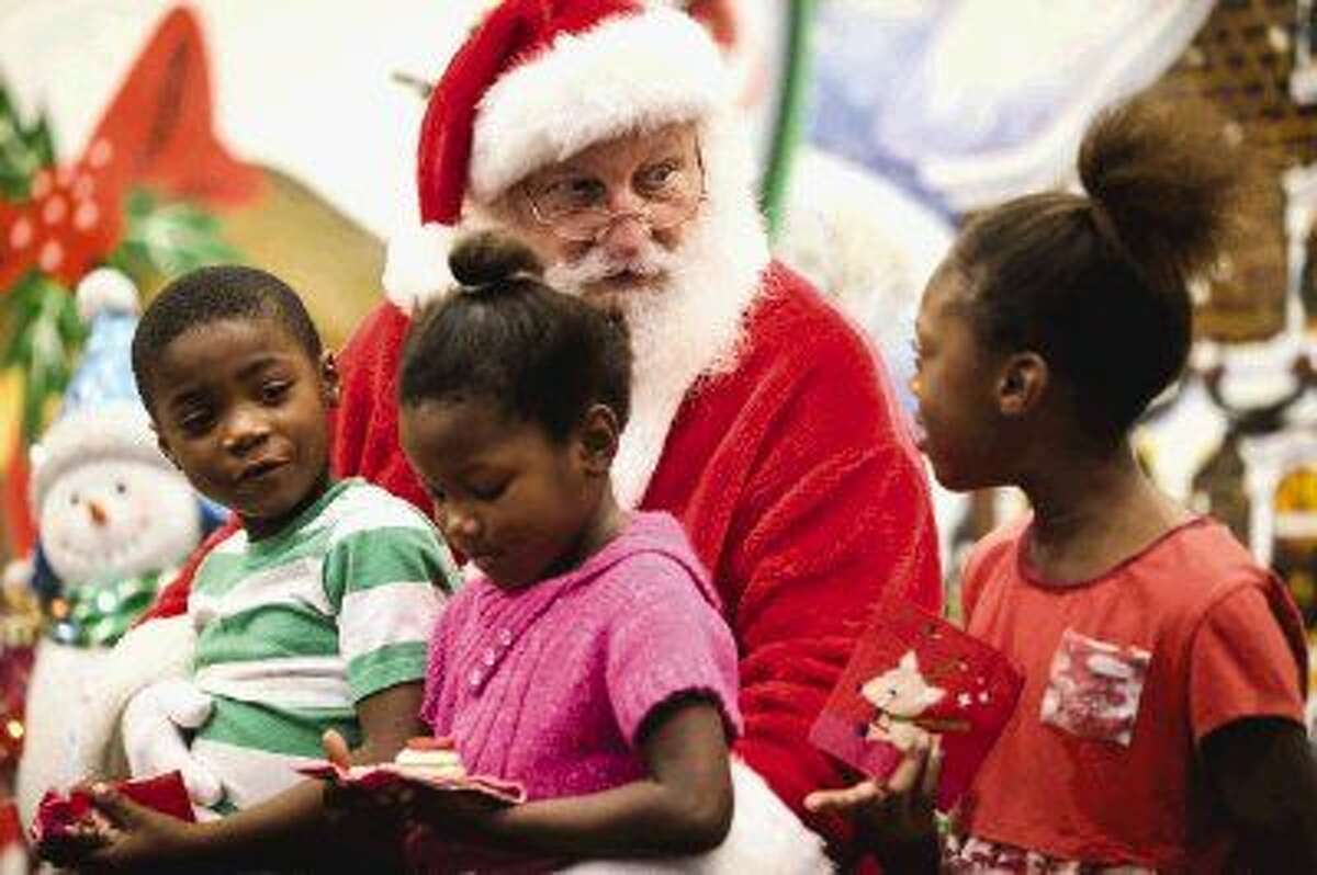 TJ Wallace, performing as Santa Claus, asks Sean Gary, 6, Layla Gary, 4, and Akasha Wilkerson, 8, what they would like for Christmas during the Gullo Christmas for Kids event on Sunday, Nov. 30, 2014, at Gullo Ford in Conroe.