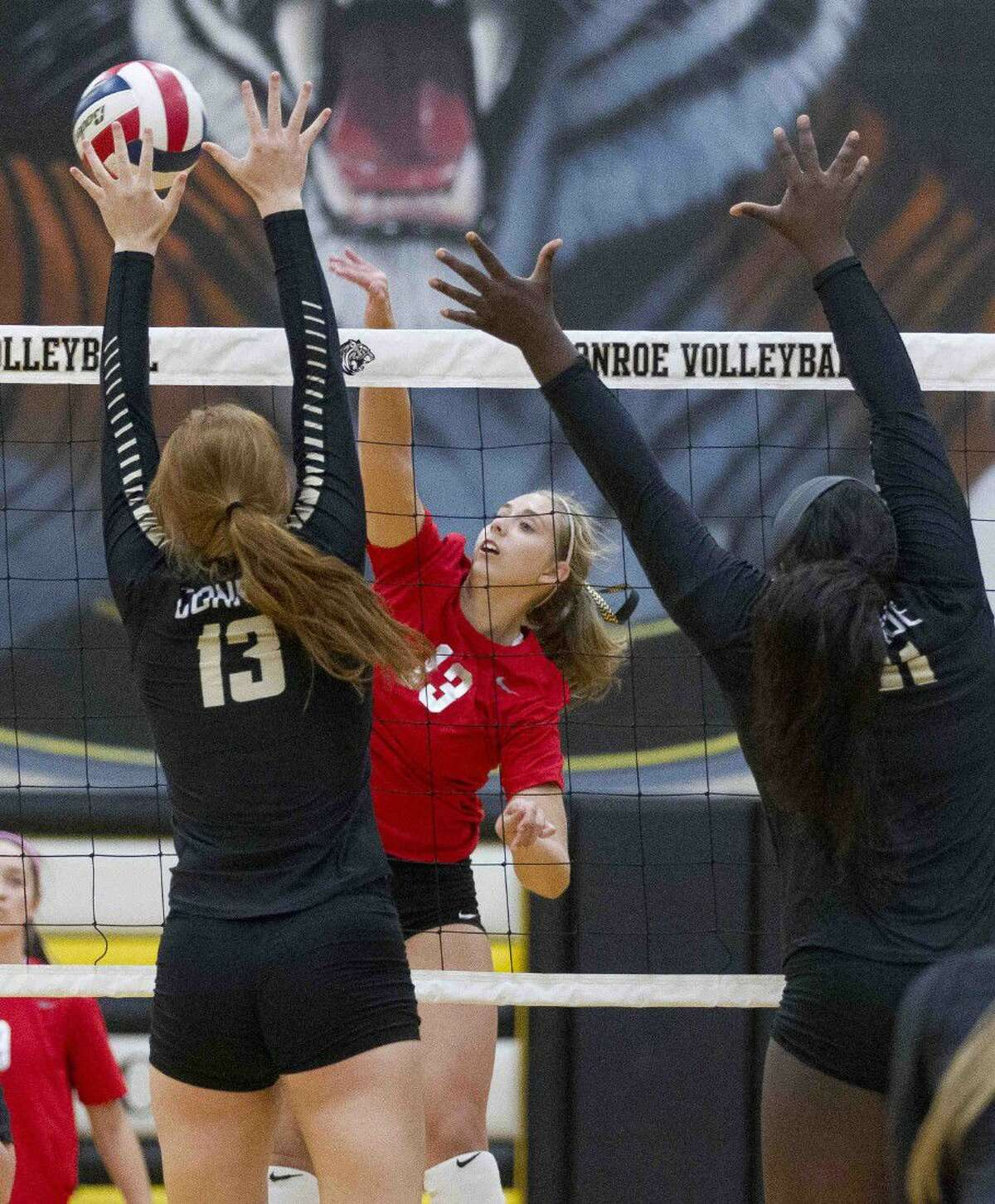 Oak Ridge outside hitter Brooke Clark (13) gets a shot past Conroe middle blocker Jozy Rodel (13) and right side hitter Tiarra Moore (51) during the first set of a District 12-6A volleyball match Tuesday, Sept. 20, 2016, in Conroe. Go to HCNpics.com to view more photos from the game.