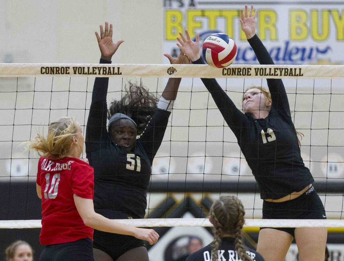 Conroe middle blocker Jozy Rodel (13) and right side hitter Tiarra Moore (51) block a shot by Oak Ridge right side hitter Hannah Mikelonis (10) during the first set of a District 12-6A volleyball match Tuesday in Conroe.