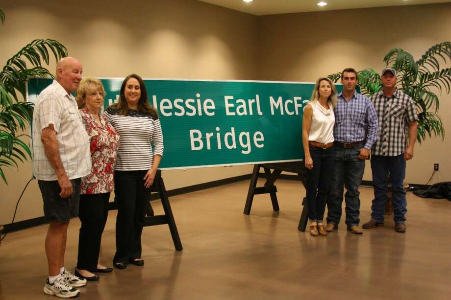 Family members of the late Liberty County Sheriff's Deputy Jesse Earl McFarland gather in front of a sign bearing his name. The sign will be placed at the northbound and southbound approaches of the bridge over the East Fork of the San Jacinto River on US 59. It was at this location in 1990 that McFarland was killed while escorting a veterans parade from Cleveland to Houston. After the unveiling of the sign on Friday at a ceremony at the Cleveland Civic Civic, it was discovered that McFarland's first name was misspelled on the signs, so they have to be corrected before being installed alongside the bridge. Photo: Vanesa Brashier