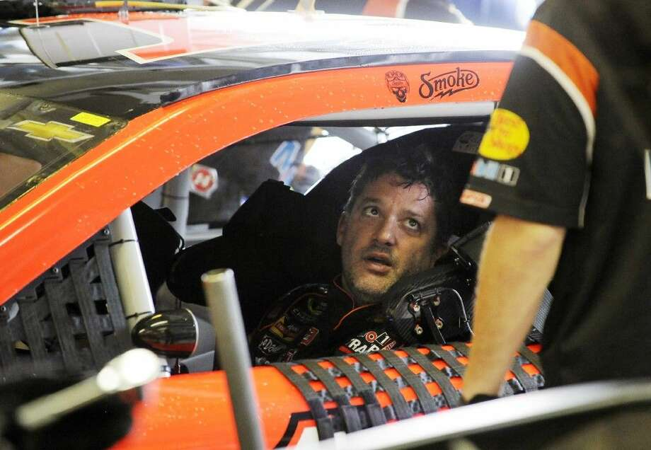 Sprint Cup Series driver Tony Stewart talks to a crew member during practice for Sunday's NASCAR race in Hampton, Georgia.
