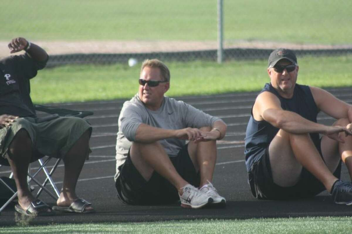 Pearland head football coach Tony Heath (center) and new defensive coordinator James Farmer watch the Oilers' 7-on-7 football game against La Porte Monday night.