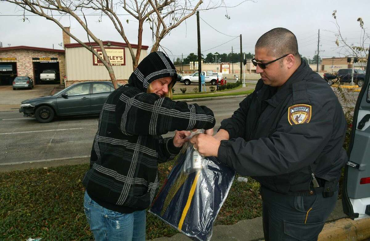 Harris County Sheriff's Office Deputy and Homeless Outreach Team member Luke Ditta, right, hands a blanket and other items to a homeless resident at the intersection of FM 1960 and Kuykendahl in January 2015.
