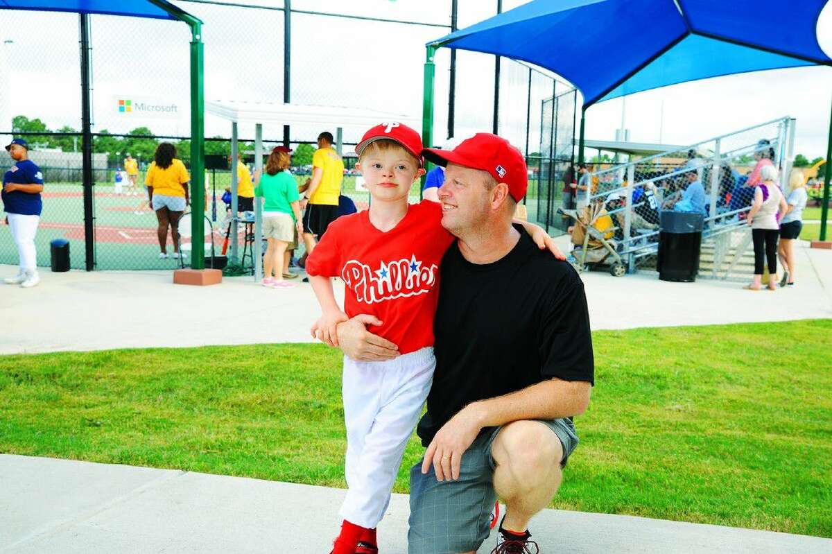 Landon Duncan, left, gets a pep talk from his father Randall Duncan before the start of a game in the Miracle League at the Langham Creek Family YMCA. The league's mission is to provide opportunities for children with disabilities to play Miracle League baseball, regardless of their abilities.