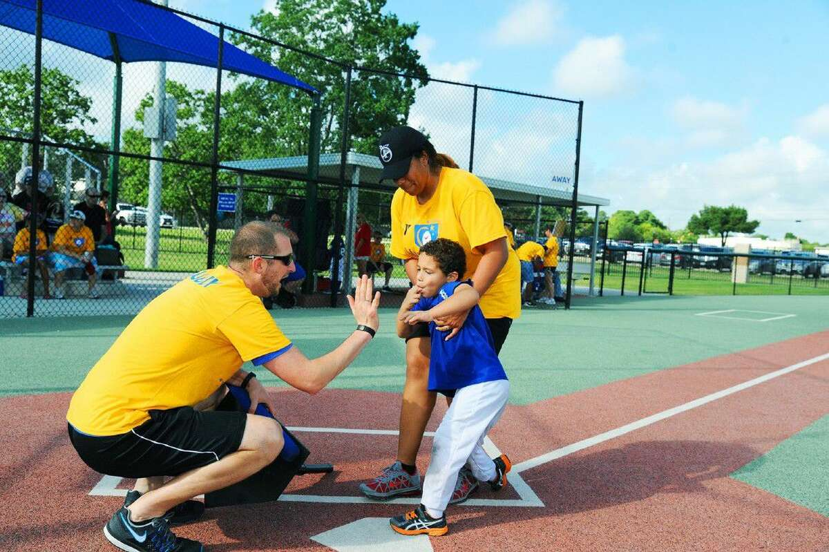 Director Matt Thompson, left, meets Gabriel Pichardo as he crosses home plate with help from Alana Chung during a Miracle League game at the Langham Creek Family YMCA. The league's mission is to provide opportunities for children with disabilities to play Miracle League baseball, regardless of their abilities.