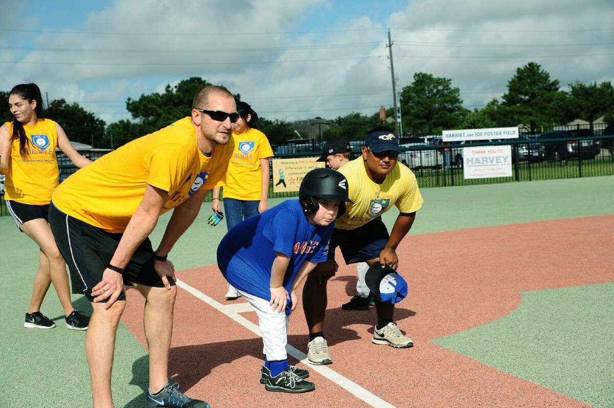 YMCA special needs director Matt Thompson, left, watches as Robert Wagne prepares to head from third base to home with help from Jordan Garcia, right, during a Miracle League game at the Langham Creek Family YMCA. The league's mission is to provide opportunities for children with disabilities to play Miracle League baseball, regardless of their abilities.