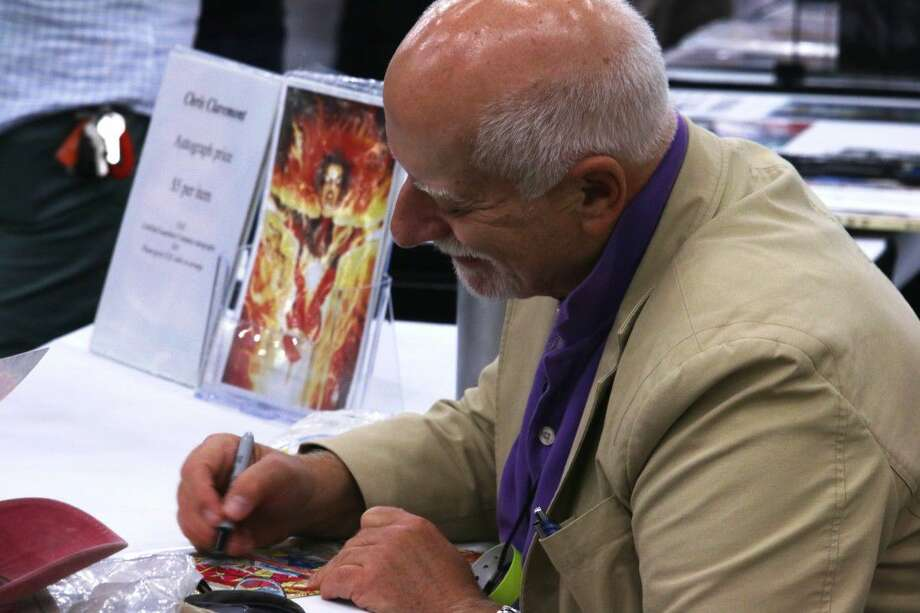 """Headliner Chris Claremont, prolific writer of Marvel's """"X-Men"""" series and creator of many popular characters, signs autographs at his booth Saturday at Amazing Houston Comic Con."""