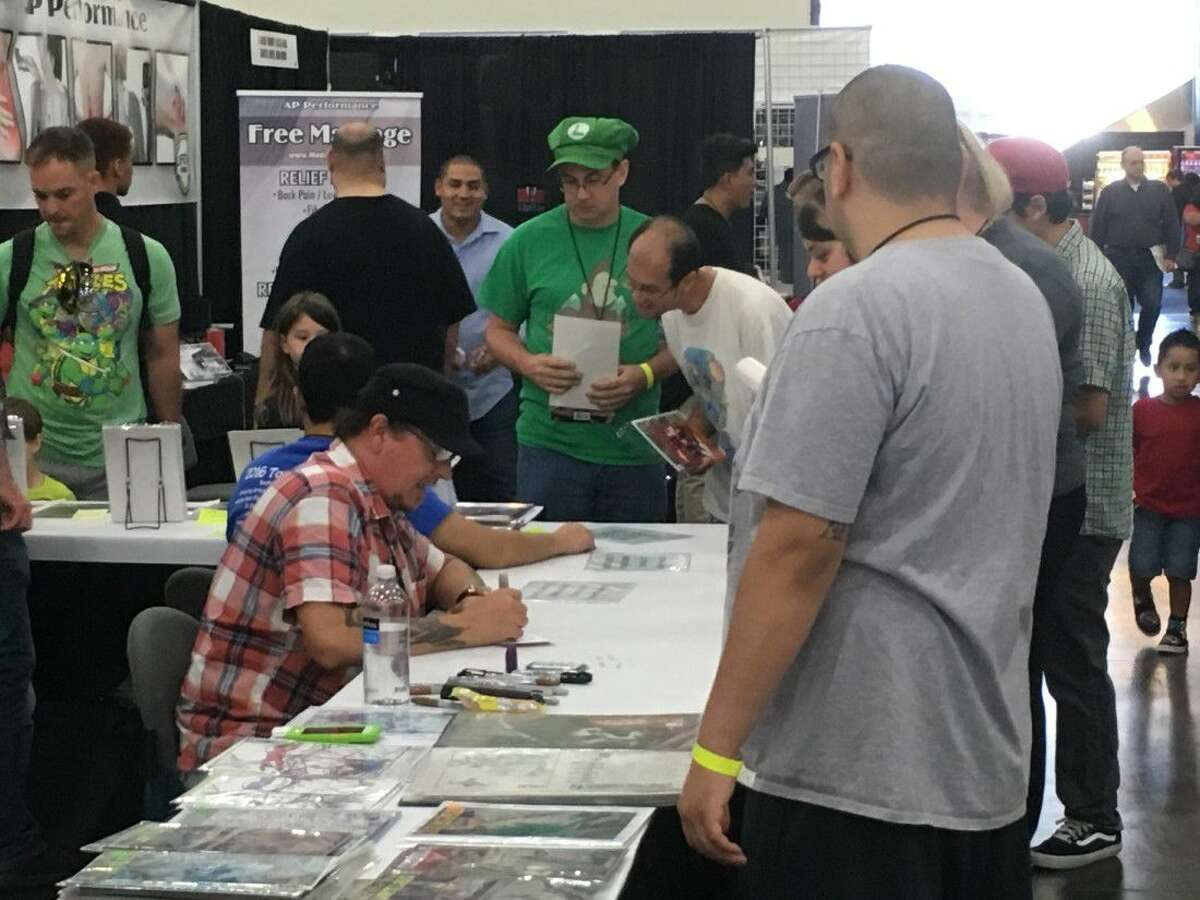 Headliner Kevin Eastman, co-creator of the popular Teenage Mutant Ninja Turtles series, signs autographs for fans at his table Sunday at Amazing Houston Comic Con.