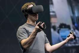 Mark Zuckerberg, chief executive officer and founder of Facebook Inc., demonstrates an Oculus Rift virtual reality (VR) headset and Oculus Touch controllers as the gives a demonstration during the Oculus Connect 3 event in San Jose, California, U.S., on Thursday, Oct. 6, 2016. Facebook Inc. is working on a new virtual reality product that is more advanced than its Samsung Gear VR, but doesn't require connection to a personal computer, like the Oculus Rift does. Photographer: David Paul Morris/Bloomberg
