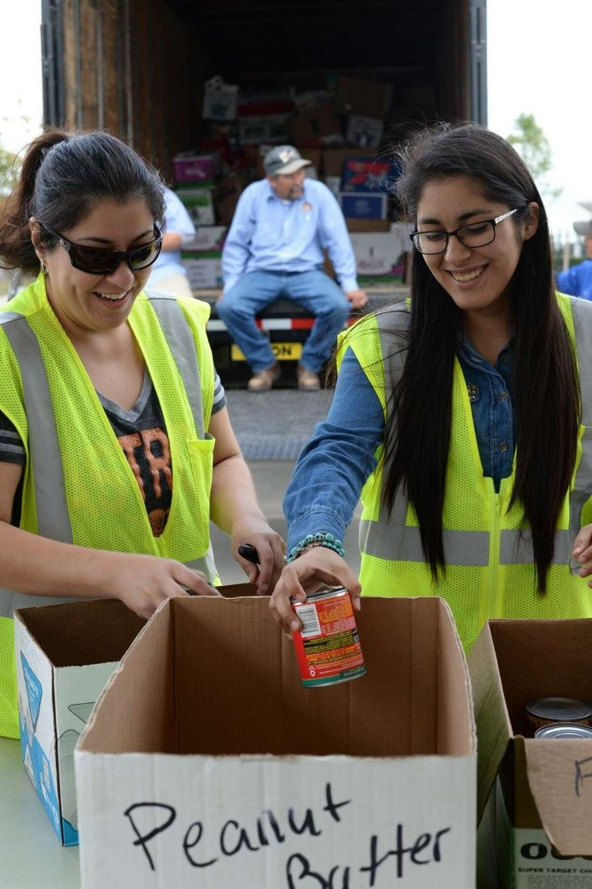 Volunteer Cynthia Navarro, left, found out about the food drive on a sign, and wanted to be part of it. Her daughter joined the volunteer team after school.