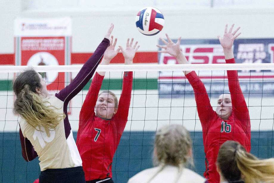 The Woodlands blockers Kayce Wright (7) and AJ Koele (16) go up to block a shot by Tarkington outside hitter Anne Crane (10) during the third set of a non-district volleyball game Tuesday at The Woodlands High School. The Woodlands swept Tarkington 3-0.
