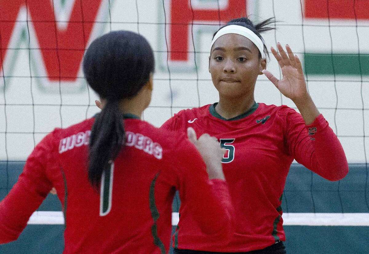 The Woodlands' Sydney Jackson (15) celebrates with Skylar Scott (1) after a kill shot during the third set of a non-district volleyball game Tuesday at The Woodlands High School. The Woodlands swept Tarkington 3-0.