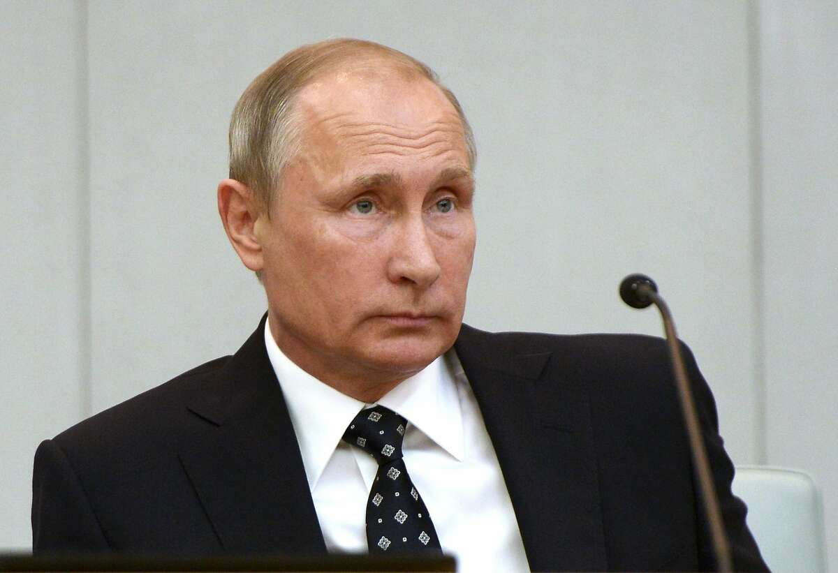 In this Oct. 5, 2016, photo, Russian President Vladimir Putin listens during the opening session of the newly elected State Duma, Russia's lower house of parliament, in Moscow, Russia. The U.S. on Oct. 7 blamed the Russian government for the hacking of political sites and accused Moscow of trying to interfere with the upcoming presidential election. Pressure has been mounting on the Obama administration to call out Russia for the hacking of U.S. political sites and email accounts. The hacking claim Friday was another setback in already strained U.S.-Russia relations.