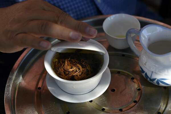 Roy Fong, owner of Imperial Tea Court, uses a cups lid to add a certain amount of stirs to brewing Kumun black ta leaves, on his farm in Esparto, CA Thursday, October 6, 2016.