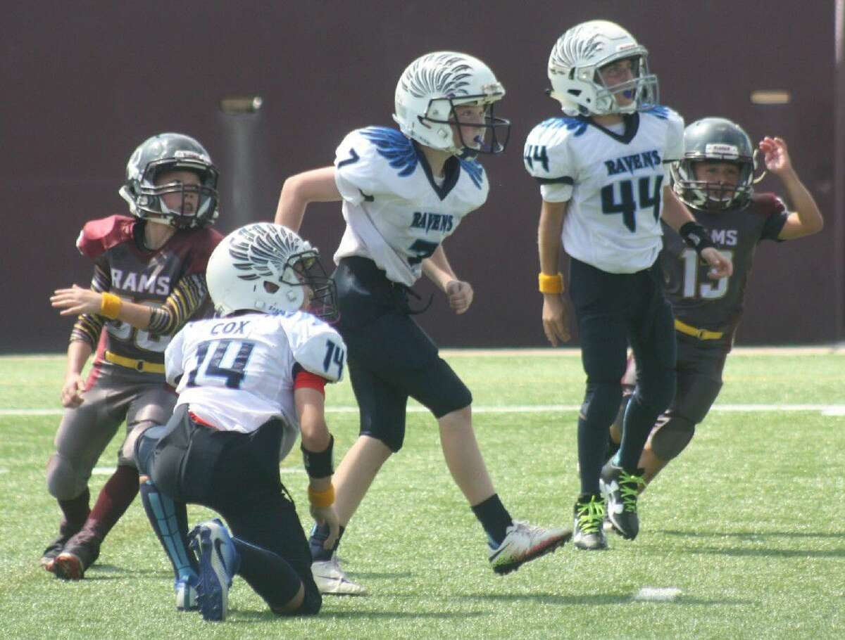 Jax Venetoulias (7) watches the outcome to his bid at a 17-yard field goal Saturday afternoon at Clyde Abshier Stadium. The 10-year-old put plenty of height and distance on the kick, but it sailed wide left by only a foot or so. Jax became the first member of the Venetoulias family since 1988 to attempt a field goal at the stadium. Looking on are teammates Kaden Cox, his holder and Hayden Smith (44).