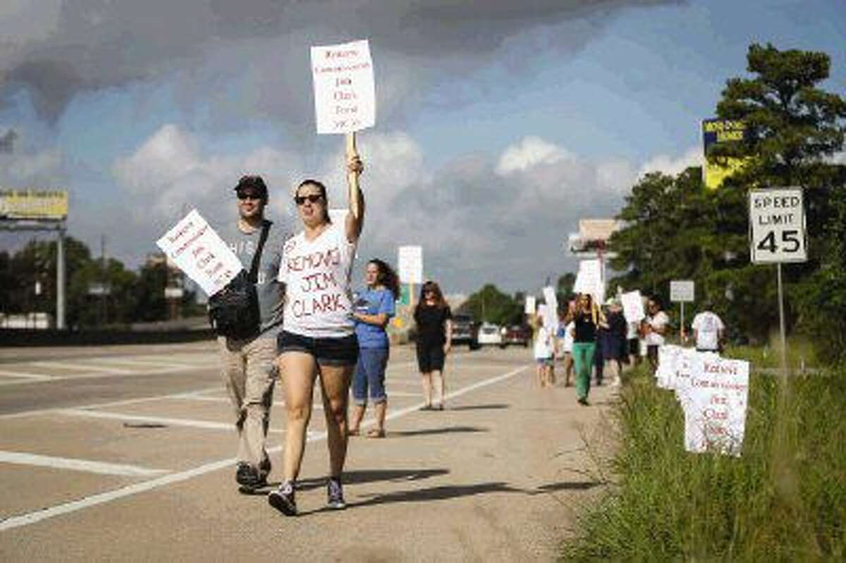 Maria Vela and John Ginn march along the side of SH 242 with protest signs on Sunday outside of the Montgomery County Animal Shelter.