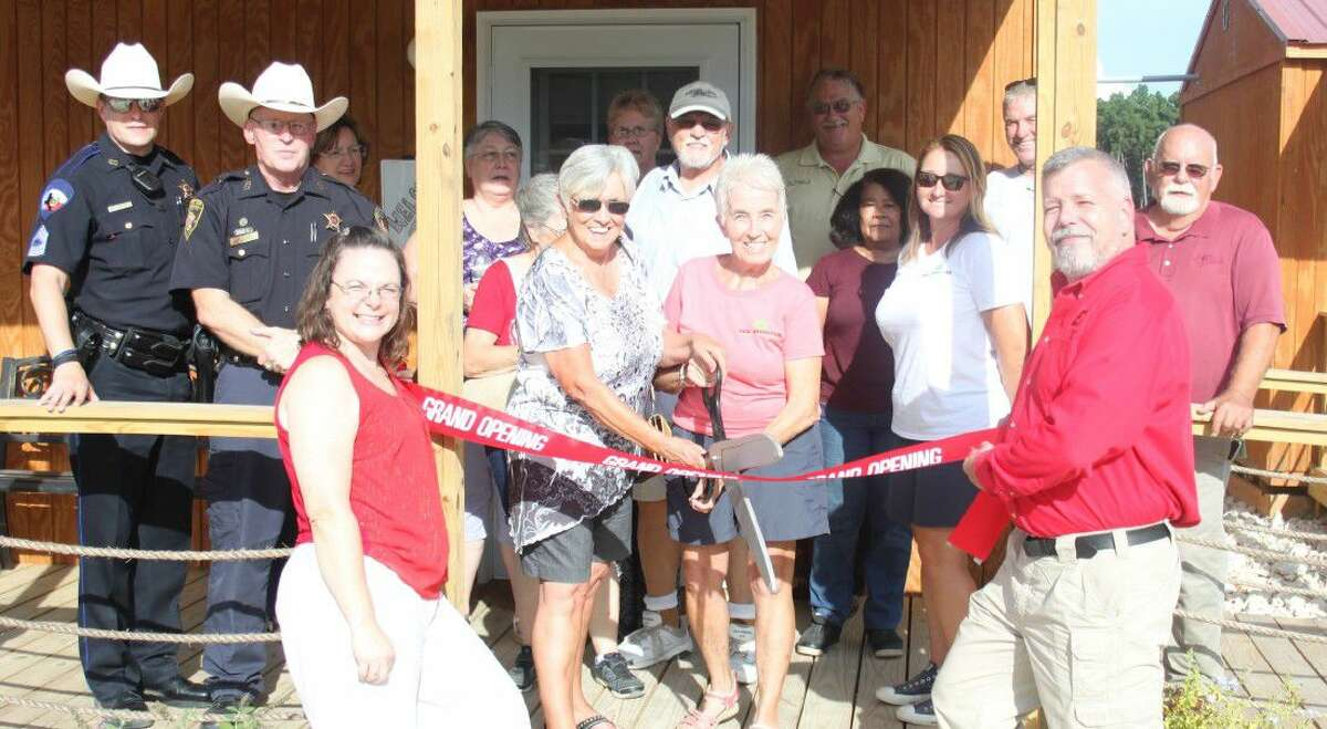 Barbara Rochester prepares to cut the ribbon to commemorate New Adventure RV Park and Horse Hotel joining the Coldspring/San Jacinto County Chamber of Commerce on Sept. 16. The park is co-owned by Rochester, her son, Rick Snyder, and his wife, Bridgette Snyder.