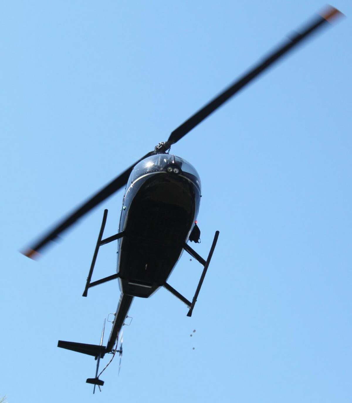 A helicopter looms above the crowd at the Terry Vaughan Classic annual golf tournament. The passengers dump out golf balls into the crowd and the person with the golf ball closest to the pin gets half of the money raised at the event.