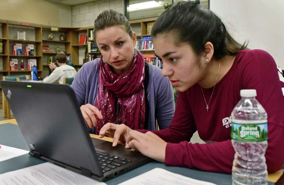Norwalk High School English teacher, Maja Hodzic works with senior, Ariana McNulty, as the Norwalk Education Foundation's college and career readiness initiative holds a college essay mentoring workshop Friday, October 7, 2016, at the school in Norwalk, Conn. Photo: Erik Trautmann / Hearst Connecticut Media / Norwalk Hour