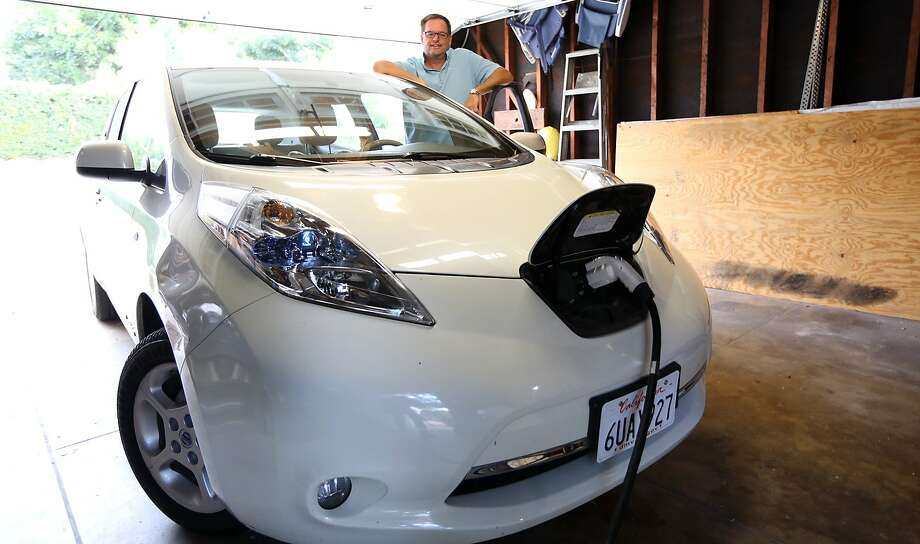 Brian Feeney charges his new electric Nissan Leaf, in his garage at home in Pasadena. He had to take delivery by tow truck because the dealership was more than 100 miles away, beyond the car's battery range.