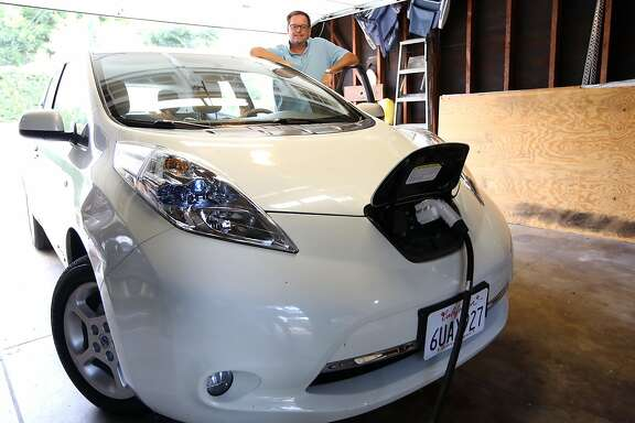 Brian Feeney with his new Nissan Leaf, an electric car. Photos show Feeney at the charging station in his home garage. Photos by Iris Schneider, October 5, 2016.