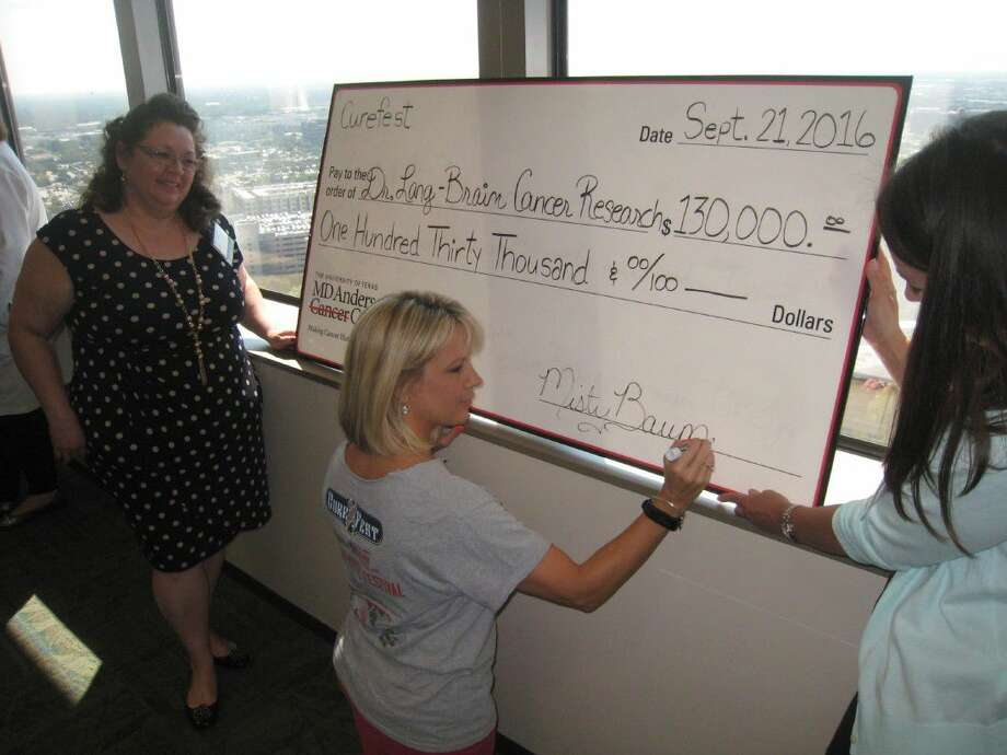 Misty Baumann signs the check Sept. 21 before the presentation of $130,000 to Dr. Frederick Lang for continued brain cancer research at University of Texas M.D. Anderson Cancer Center.