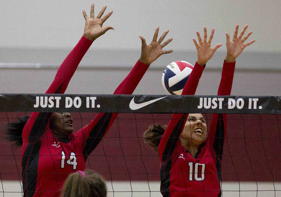Fort Bend Austin's Tia Smith and Emily Jaroszewski try to block a shot in the first set of a volleyball match against Oak Ridge during the Katy/Cy-Fair Nike Invitational Friday. Go to HCNpics.com to purchase this photo and others like it. Photo: Jason Fochtman