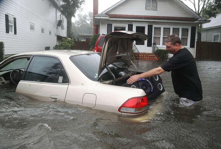 ST AUGUSTINE, FL - OCTOBER 07:  Rob Birch salvages a speaker from the trunk of his car which floated out of his drive way as Hurricane Matthew passes through the area on October 7, 2016 in St Augustine, Florida.  Florida, Georgia, South Carolina and North Carolina all declared a state of emergency in anticipation of Hurricane Matthew. (Photo by Joe Raedle/Getty Images) *** BESTPIX *** Photo: Joe Raedle
