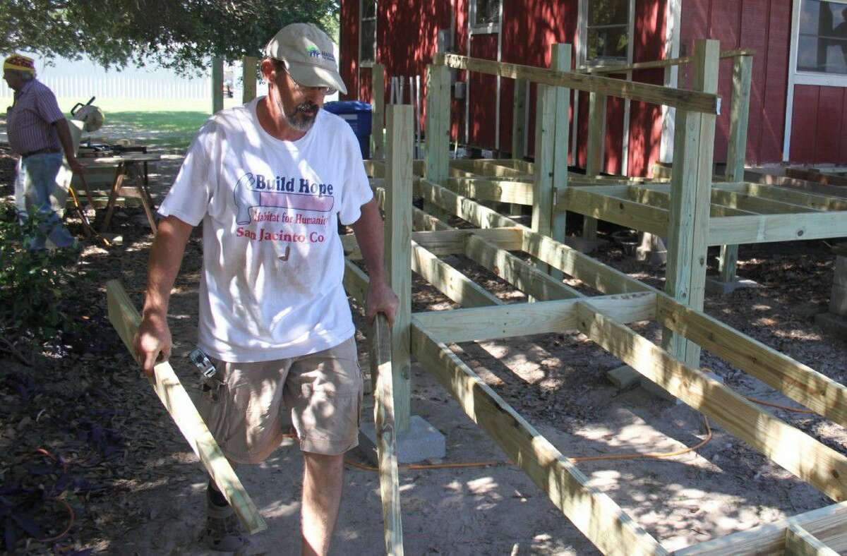 Sean Hanson sets up boards to create an ADA compliant ramp for the Coldspring/San Jacinto County Chamber of Commerce office.
