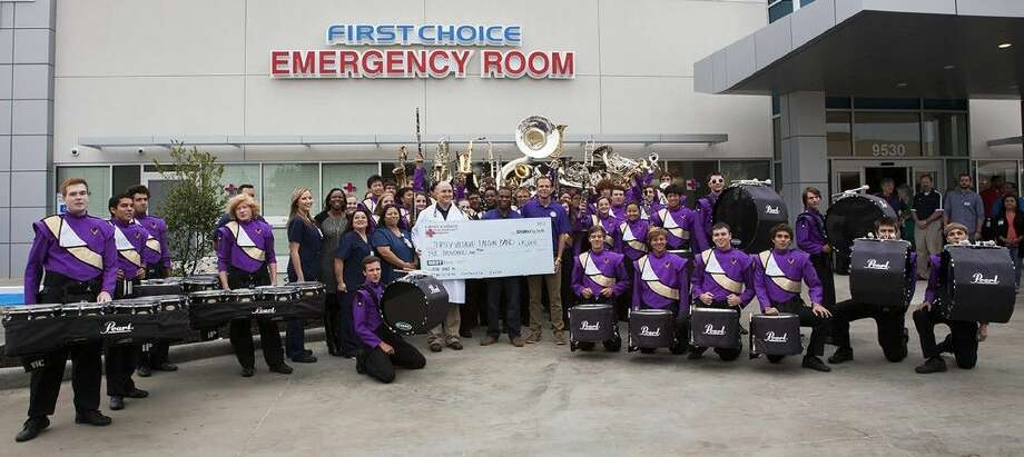 Representatives from First Choice Emergency Room present the Jersey Village High School band with a $5,000 check during the ribbon cutting of the Jones Road FCER facility on Nov. 6. Photo: Submitted Photo
