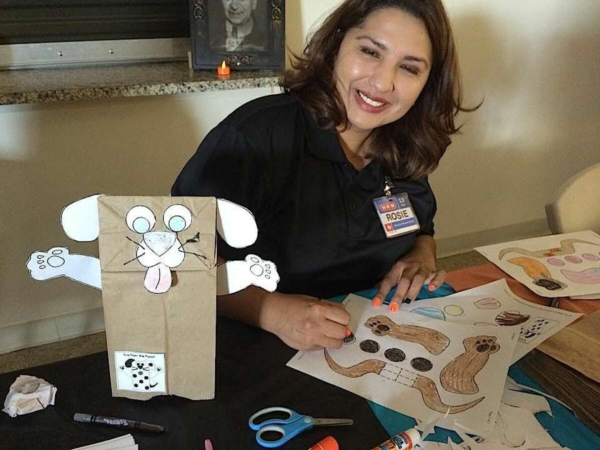 H-E-B volunteer Rosie Garcia helps the kids make puppets (photo courtesy of Anna Bryant).